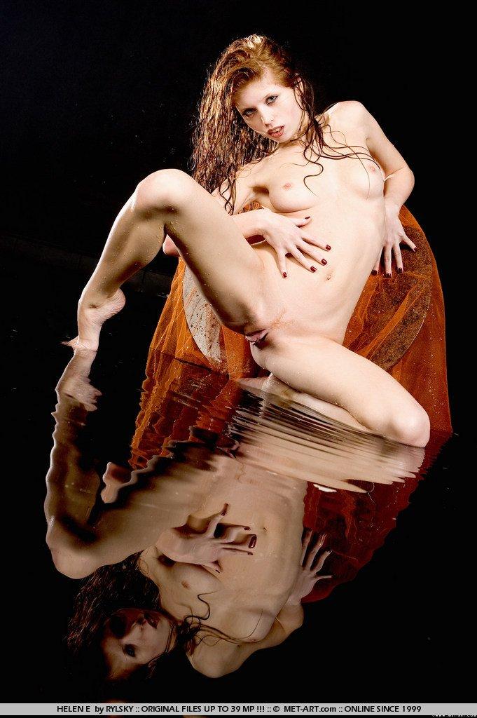 Рыженькая и нагая фотомодель с красивой формы ухоженной пиздой Helen E демонстрирует подтянутое мокрое туловище